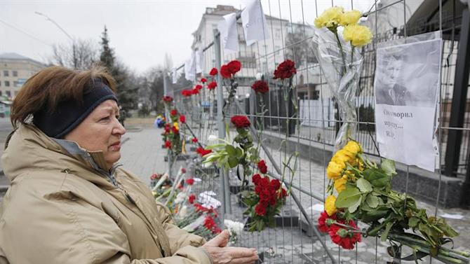 RPI02. Kiev (Ukraine), 28/02/2015.- A woman looks at a portrait of Boris Nemtsov which is fixed on a metal fence alongside flowers in memory of Boris Nemtsov, slain Russian opposition leader, in front of Russian embassy in Kiev, Ukraine, 28 February 2015. Russian opposition leader Boris Nemtsov was shot dead from a passing car on the Bolshoy Kammeny bridge in central Moscow late in the evening of 27 February 2015. (Rusia, Ucrania, Moscú) EFE/EPA/ROMAN PILIPEY