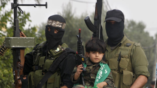 A Palestinian boy and militants of the Izzedine Al-Qassam Brigades, the armed wing of Hamas, attend funerals of five Hamas militants in Mugharka village, central Gaza Strip, Thursday, Nov. 22, 2012. Five Hamas militants were killed in an Israeli air strike yesterday, Palestinian health officials said. (AP Photo/Adel Hana)