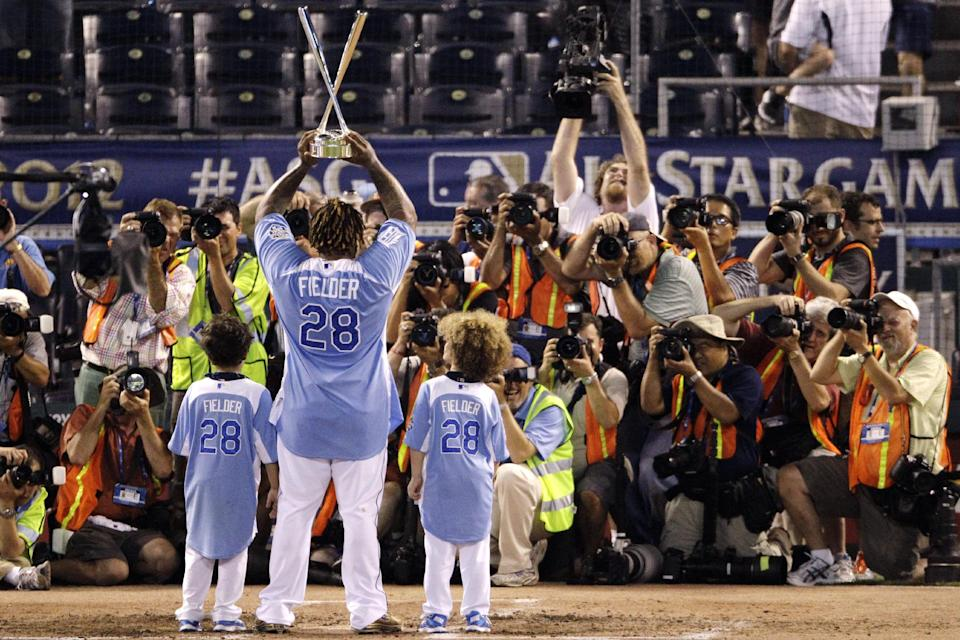 Photographers gather as American League's Prince Fielder, of the Detroit Tigers, poses with his children Haven, left, and Jaden after receiving the MLB All-Star baseball Home Run Derby trophy, Monday, July 9, 2012, in Kansas City, Mo. (AP Photo/Charlie Neibergall)