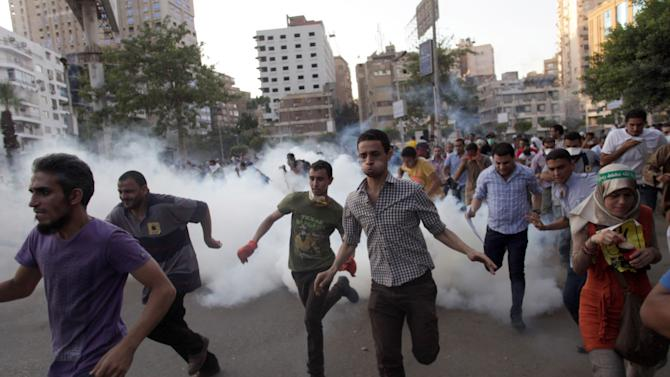Supporters of Egypt's ousted President Mohammed Morsi, run for cover from tear gas fired by police, not seen, during a protest in Cairo, Egypt, Friday, Aug. 30, 2013. Tens of thousands of protesters and Muslim Brotherhood supporters rallied Friday throughout Egypt against a military coup and a bloody security crackdown, though tanks and armored police vehicles barred them from converging in major squares. (AP Photo/Khalil Hamra)