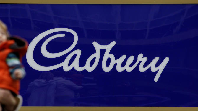 FILE - This is a Tuesday, Jan. 19, 2010 file photo of  a woman  as she carries a child past a logo outside the headquarters of Cadbury in Birmingham, England. While the United States and many European countries have strict regulations barring foreign control of many businesses, Britain has been largely content in the belief it has more to gain than lose from its relaxed takeover rules. But last year's controversial $21.4 billion takeover by Kraft Foods Inc. of 195-year-old Cadbury PLC, maker of the Dairy Milk bar, stirred up nationalist sentiment and prompted the government to consider a tightening of the legislation. (AP Photo/Matt Dunham, File)