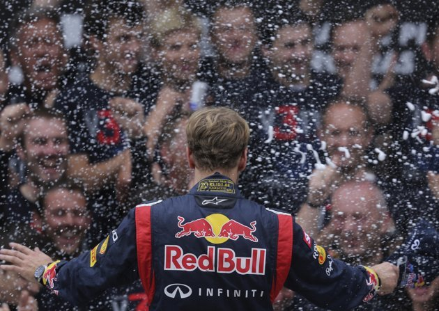 Red Bull Formula One driver Sebastian Vettel of Germany celebrates winning the world championship on the podium with his team after the Brazilian F1 Grand Prix
