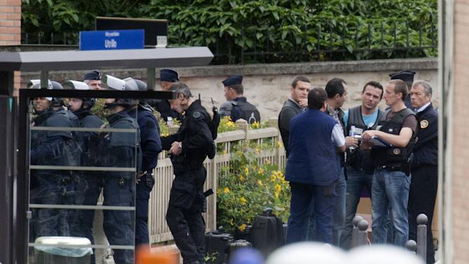 Police officers surround a school complex where an armed man took hostages Tuesday, July 10, 2012 in Vitry sur Seine, south of Paris. Children were initially among the hostages, but the man appears to now be holding one adult. One police official said the man was carrying a gun; others said they did not know what weapon he had. The police official said officers from the elite Raid force were on site to negotiate with the man. (AP Photo/Jacques Brinon)