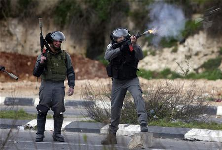 An Israeli border policeman fires rubber bullets at stone-throwing Palestinian protesters during clashes outside Israel's Ofer military prison near the West Bank city of Ramallah February 22, 2013. Israeli forces clashed with Palestinian protesters throughout the occupied West Bank on Friday, capping a week of violence amid a hunger strike by four Palestinians in Israeli jails. REUTERS/Mohamad Torokman
