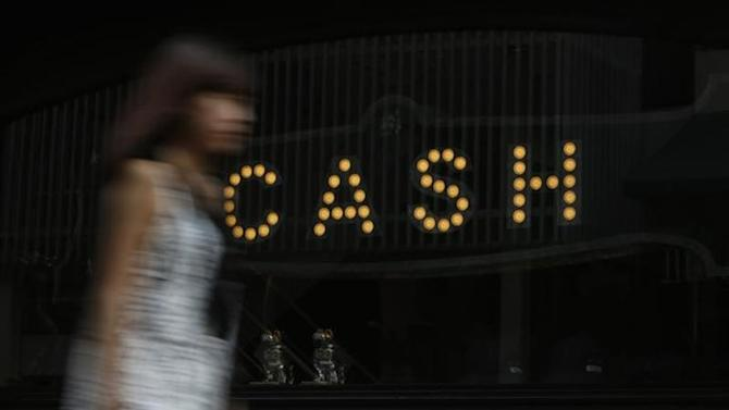 """A woman walks past the word """"CASH"""", part of a sign, on a street in Tokyo August 29, 2013. REUTERS/Yuya Shino"""