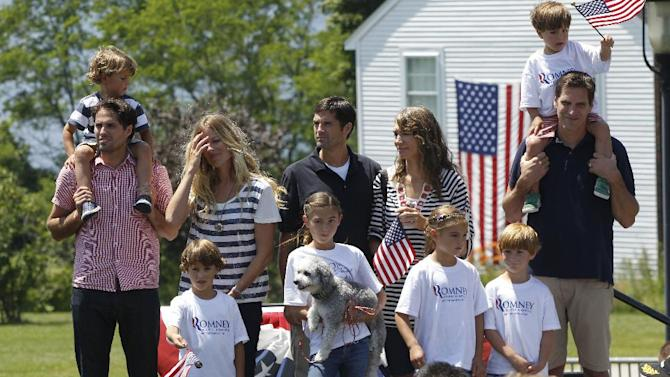 """In this July 4, 2012 photo, Craig Romney, left, Matt Romney, center, and Josh Romney, right, sons of Republican presidential candidate Mitt Romney, stand with other family members at Brewster Academy during a rally at the end of the Fourth of July Parade in Wolfeboro, N.H.  Romney's large family is at the center of his life _ and of his presidential campaign. At a time when nontraditional families have become the norm _ and when even the Romneys are watching """"Modern Family,"""" a popular sitcom that centers on unconventional family arrangements _ the Romney brood stands out. (AP Photo/Charles Dharapak)"""