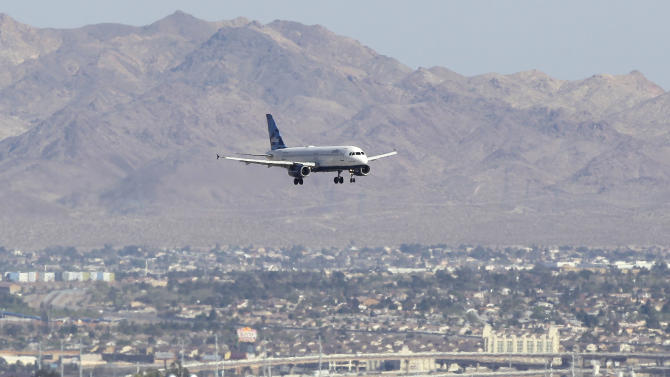 """Jet Blue flight 191 from New York makes its approach to McCarran International Airport, Tuesday, March 27, 2012, in Las Vegas. The captain of the plane stormed through his plane rambling about a bomb and threats from Iraq on Tuesday until passengers on the Las Vegas-bound flight tackled him to the ground just outside the cockpit, passengers said. The captain was taken to a hospital after suffering a """"medical situation"""" on board that forced an emergency landing in Amarillo, Texas, the airline said. (AP Photo/Julie Jacobson)"""