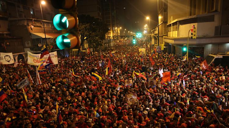 Supporters of President Hugo Chavez gather next to the Miraflores presidential palace as they celebrate in Caracas, Venezuela, Sunday, Oct. 7, 2012. Venezuela's electoral council said late Sunday President Hugo Chavez has won re-election, defeating challenger Henrique Capriles. (AP Photo/Rodrigo Abd)