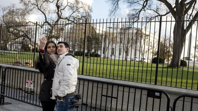 Tourists take pictures of themselves in front of the White House on Thanksgiving Day in Washington
