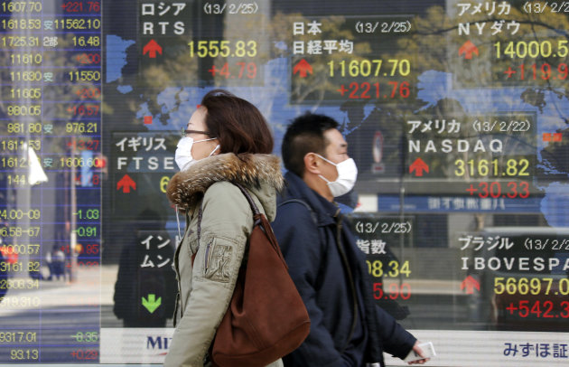 People walk by an electronic stock board of a securities firm in Tokyo, Monday, Feb. 25, 2013.  Japanese stocks led Asian markets higher Monday, jumping on a report that the prime minister's pick for