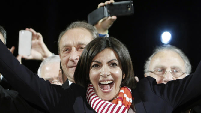 French Socialist Party deputy mayor of Paris, Anne Hidalgo, center, smiles, as outgoing mayor Bertrand Delanoe, stands behind her, during a speech after results were announced in the second round of the French municipal elections, in Paris, Sunday, March 30, 2014. Hidalgo saved Paris for the flagging Socialist Party in Sunday's municipal elections, becoming the French capital's first female mayor. (AP Photo/Thibault Camus)