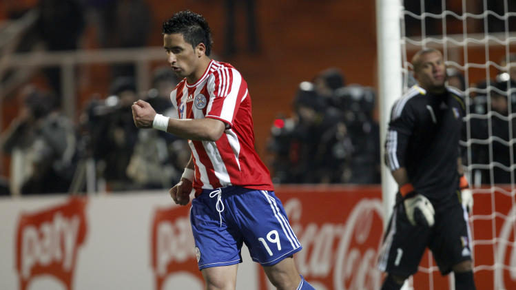 Paraguay's Lucas Barrios celebrates after scoring in a penalty shootout as Venezuela's goalkeeper Renny Vega reacts during a Copa America semifinal soccer match in Mendoza, Argentina, Thursday, July 21, 2011. After the match ended 0-0 in extra time, Paraguay won 5-3 on penalties. (AP Photo/Ramon Espinosa)