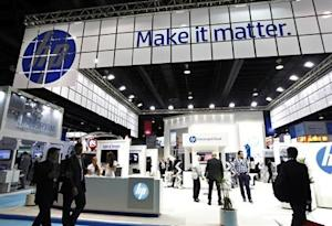 People walk past a Hewlett-Packard stand during the Gulf Information and Technology Exhibition at the Dubai World Trade Centre