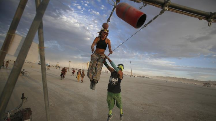 "Gwen Barker and Rezwan Khan play on a swing art installation during the Burning Man 2014 ""Caravansary"" arts and music festival in the Black Rock Desert of Nevada"