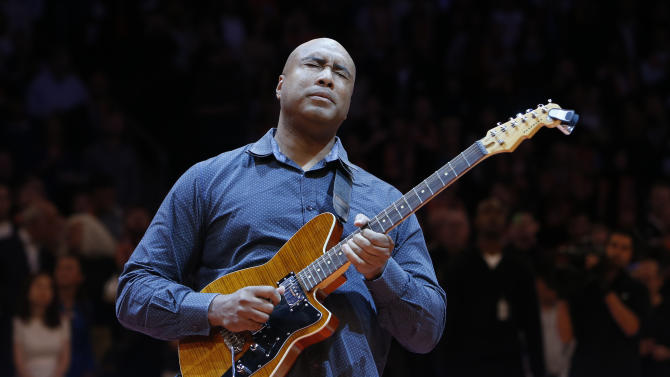 FILe - In this Feb. 1, 2014, file photo, former New York Yankee baseball player Bernie Williams plays the nation anthem on a guitar before an NBA basketball game between the Miami Heat and the New York Knicks, in New York. Williams stopped being a baseball player in 2006. Since age 7, he hasn't stopped being a musician. His father brought a guitar back from a trip to Spain while serving in the Merchant Marines, and Williams fell in love with music after learning the first few chords. (AP Photo/Jason DeCrow, File)