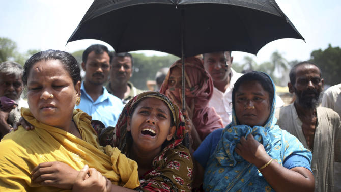 Family members cry after identifying bodies of their relatives that were retrieved from a collapsed garment factory building on Friday, May 3, 2013 in Savar, near Dhaka, Bangladesh. Authorities suspended the mayor of the suburb of Savar, where the building was located, and arrested an engineer who called for the building's evacuation last week but was also accused of helping the owner add three illegal floors to the eight-story structure. (AP Photo/Wong Maye-E)