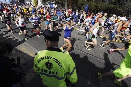 A Middlesex County Sheriff watches as runners pass by during the 118th running of the Boston Marathon in Hopkinton