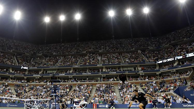 Roger Federer, of Switzerland, returns a shot to Sam Groth, of Australia, during the second round of the U.S. Open tennis tournament Friday, Aug. 29, 2014, in New York. (AP Photo/Jason DeCrow)