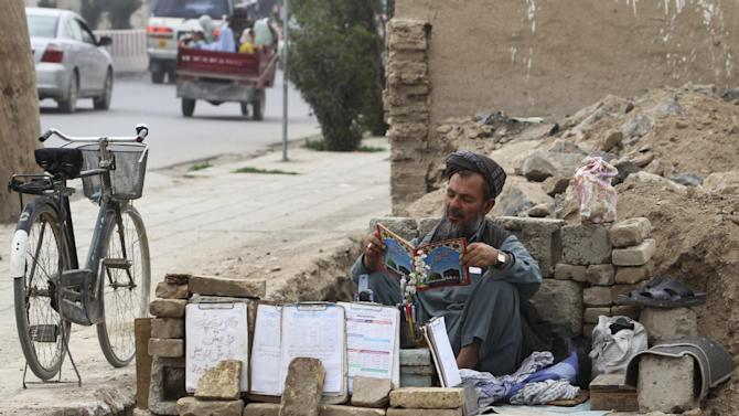An Afghan curbside vendor takes a break in Kandahar, southern Afghanistan, Tuesday, March 26, 2013. Residents of Kandahar complain of few jobs despite heavy international investment in the country since the collapse of the Taliban in 2001. (AP Photo/Allauddin Khan)
