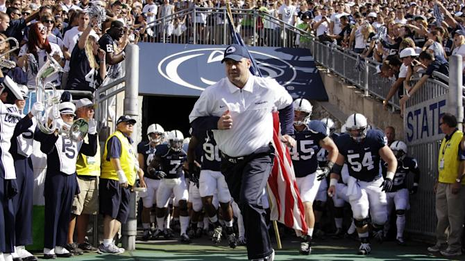 FILE - In this Sept. 15, 2012, file photo, Penn State head coach Bill O'Brien leads his team onto the field at Beaver Stadium for an NCAA college football game against Navy in State College, Pa. The reverberations from the Penn State child sex abuse scandal was selected as the sports story of the year by United States editors and news directors in an annual vote conducted by The Associated Press, marking the first time that the same issue was selected in consecutive years since the AP began announcing a sports story of the year in 1990. (AP Photo/Gene J. Puskar, File)