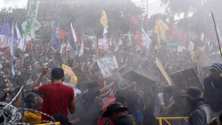 Protesters stand their ground as police try to disperse them with water cannons in Quezon city
