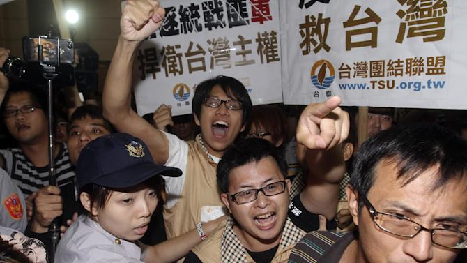 Protesters shout slogans as Zhang Zhijun, minister of Beijing's Taiwan Affairs Office, arrived at airport in Taoyuan county, Taiwan, Wednesday, June 25, 2014. China has sent Zhang, its first ever ministerial-level official to Taiwan for four days of meetings to rebuild ties with the self-ruled island that Beijing claims as its own, after mass protests in Taipei set back relations earlier this year. (AP Photo/Chiang Ying-ying)