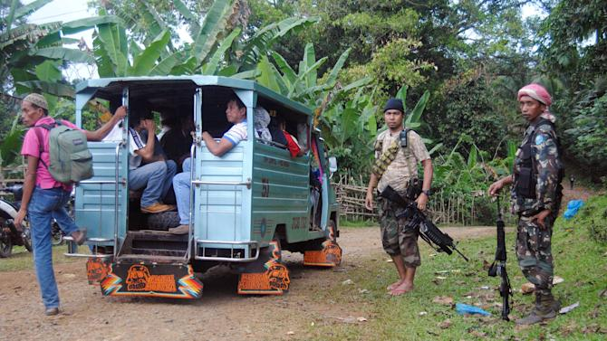In this photo taken on Thursday, Feb. 7, 2013, Moro National Liberation Front (MNLF) rebels, who signed a peace agreement with the Philippine government in 1996, man a checkpoint at a remote village on the volatile island of Jolo, Sulu province in southern Philippines. After years of fighting the government from hidden jungle bases in the southern Philippines, an Al-Qaida-linked militant group is facing a new adversary: fellow Muslim insurgents who can match their guerrilla battle tactics and are eager to regain their lost stature by fighting the widely-condemned terrorist group. The emerging enmity between the Abu Sayyaf militants and the Moro rebels could bolster a decade-long campaign by the Philippines and Western countries to isolate the al-Qaida offshoot Abu Sayyaf, which remains one of the most dangerous groups in Southeast Asia.(AP Photo/Nickee Butlangan)