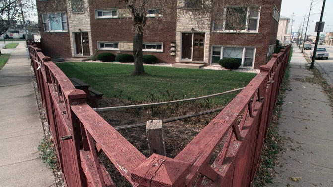 FILE - In this Nov. 22, 1998 file photo, a fence surrounds the yard of the apartment building where the mother of convicted serial killer John Wayne Gacy once lived in Chicago. Cook County Sheriff Tom Dart says his officers and the FBI using high tech equipment and two dogs trained to sniff out human remains, went to the apartment complex in March 2013 and found nothing to indicate the serial killer stashed any bodies there. Dart has been investigating the serial killer who was convicted in 1980 of murdering 33 young men in the 1970s on a number of fronts the last couple years.  (AP Photo/M. Spencer Green, File)