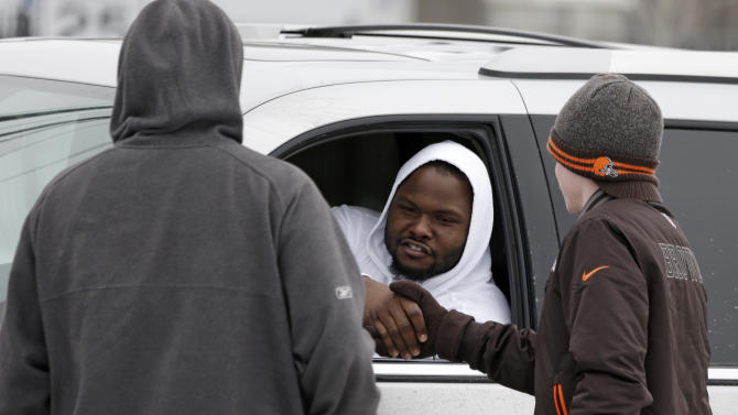 Cleveland Browns nose tackle Ahtyba Rubin shakes hands with fans outside the NFL football team's training facility Monday, Dec. 31, 2012, in Berea, Ohio. One day after ending yet another dismal season with a loss in Pittsburgh, Cleveland fired coach Pat Shurmur and general manager Tom Heckert, the first moves in what is expected to be a massive offseason overhaul by new owner Jimmy Haslam. (AP Photo/Tony Dejak)
