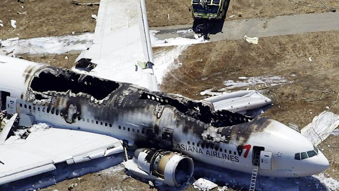 FILE - This July 6, 2013, file photo, shows the wreckage of the Asiana Flight 214 airplane after it crashed at the San Francisco International Airport in San Francisco. The pilots of Asiana Flight 214, as well as the airline, are raising the possibility that a key device that controls the Boeing 777's speed may have malfunctioned, an aviation expert familiar with the investigation into the crash said Tuesday, Oct. 8, 2013. (AP Photo/Marcio Jose Sanchez, File)