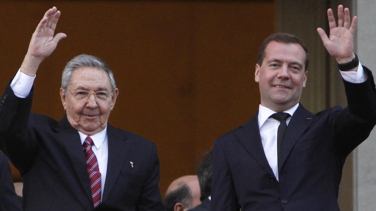 Cuba's President Raul Castro, right, and Russia's Prime Minister Dmitry Medvedev, left, wave to journalists after a wreath-laying ceremony at the Jose Marti monument in Havana, Cuba, Thursday, Feb. 21, 2013. (AP Photo/Ismael Francisco, Cubadebate)
