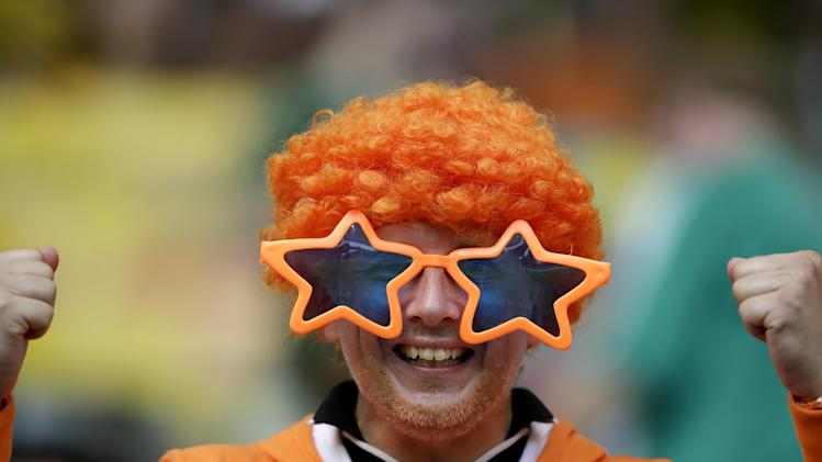 A fan of the Netherlands poses for photos before the World Cup quarterfinal soccer match between the Netherlands and Costa Rica at the Arena Fonte Nova in Salvador, Brazil, Saturday, July 5, 2014