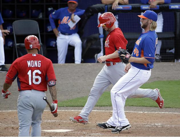 St. Louis Cardinals' Shane Robinson, second from right, scores on a wild pitch by New York Mets' Jeff Walters, right, in the eighth inning of an exhibition spring training baseball game, Wedne