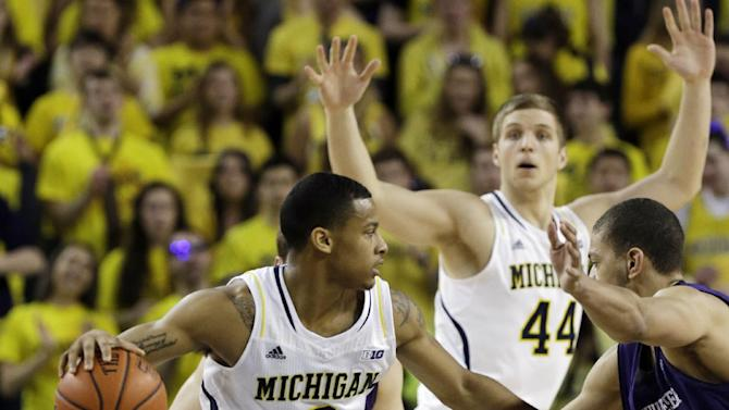 Michigan guard Trey Burke (3) looks to pass around the defense of Northwestern forward Mike Turner (10) during the first half of an NCAA college basketball game in Ann Arbor, Mich., Wednesday, Jan. 30, 2013. (AP Photo/Carlos Osorio)