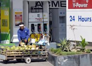 This file photo taken on April 10, 2008 shows a street vendor selling coconuts outside a petrol station in Manila. The Philippines is the world&#39;s biggest exporter of coconut products. Supply is not a problem, with 350 million coconut trees growing from the beaches up to the hills and yielding 15 billion fruits a year