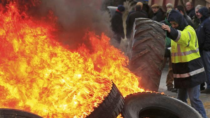 A French farmer rolls a tyre onto burning ones to protest falling prices as they block the road near a Lidl supermarket logistics warehouse in Sailly-lez-Cambrai
