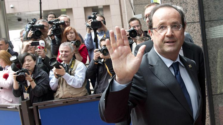 French President Francois Hollande, right, waves to journalists as he arrives for an EU summit in Brussels on Thursday, June 27, 2013. European Union leaders meet in Brussels ostensibly to agree on ways to find more jobs for the young, who've been disproportionately punished by years of crisis and recession. (AP Photo/Geert Vanden Wijngaert)