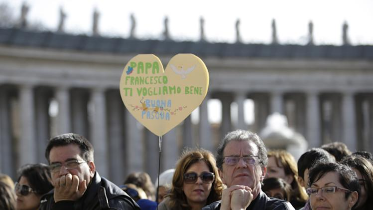 "Faithful hold a heart shaped banner reading in Italian ""Pope Francis we love you. Happy Easter"" in St. Peter's square at the Vatican on the occasion of the celebration of the Easter mass Sunday, March 31, 2013. ""Our daily problems and worries can wrap us up in ourselves, in sadness and bitterness, and that is where death is,"" he said. ""Let the risen Jesus enter your life, welcome him as a friend, with trust: he is life!"" said Pope Francis during the Easter vigil. (AP Photo/Andrew Medichini)"