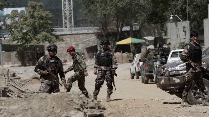 Afghan security force members investigate nearby the entrance gate of the presidential palace in Kabul, Afghanistan Tuesday, June 25, 2013. Suicide attackers blew up a car bomb and battled security forces outside Afghanistan's presidential palace Tuesday after infiltrating one of the most secure areas of the capital. The Taliban claimed responsibility for the Kabul palace attack, which came as reporters were gathering for a news event on Afghan youth at which President Hamid Karzai was expected to talk about ongoing efforts to open peace talks with the militant group. (AP Photo/Rahmat Gul)