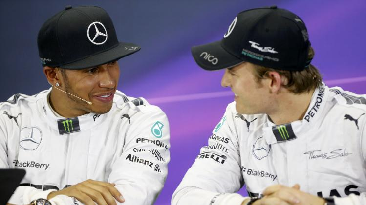 Mercedes Formula One driver Hamilton of Britain talks with teammate, Mercedes Formula One driver Rosberg of Germany during a news conference after the qualifying session for the Australian F1 Grand Prix in Melbourne