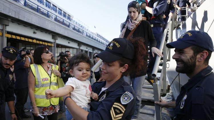 "A crew member of the Greek frigate ""Salamis"" carries a baby at the port of Piraeus near Athens"