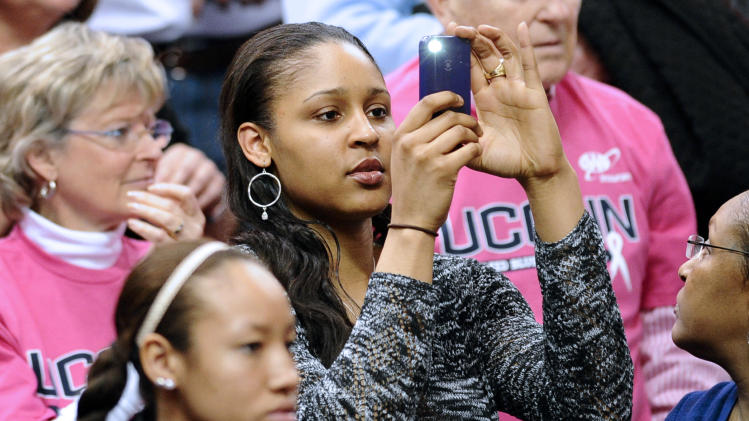 Connecticut alum and Minnesota Lynx WNBA player  Maya Moore takes a photo with during the first half of an NCAA college basketball game between Connecticut and Baylor in Hartford, Conn., Monday, Feb. 18, 2013. Baylor won 76-70. (AP Photo/Jessica Hill)