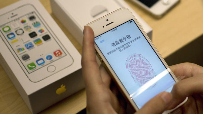 FILE - The Sept. 20, 2013 file photo shows a customer configuring the fingerprint scanner technology built into iPhone 5S at an Apple store in Wangfujing shopping district in Beijing. The fingerprint-based security system used to unlock Apple's latest iPhone can be bypassed using a household printer and some wood glue, a German hacking group has claimed. A spokesman for the Chaos Computer Club said Monday, Sept. 23, 2013 the group managed to fool the biometric sensor in the iPhone 5S over the weekend by creating an artificial copy of a genuine fingerprint. (AP Photo/Andy Wong)