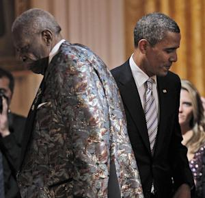 President Barack Obama, right, walks back to his seat after helping B.B. King, left, on stage to perform during the White House Music Series saluting Blues Music in recognition of Black History Month, Tuesday, Feb. 21, 2012, in the East Room of the White House in Washington. (AP Photo/Pablo Martinez Monsivais)