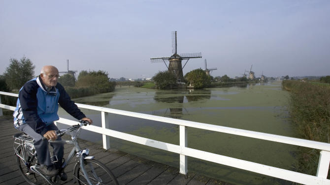 "FILE - In this Oct. 11, 2007 file photo a Dutch man rides his bike in front of windmills in Kinderdijk, Netherlands. While tax hikes and budget cuts have led to partisan warfare in the U.S. and widespread strikes in Southern Europe, in 2013 the Netherlands is weathering ""austerity"" with relative grace. Some say that's because the country is experiencing a renaissance of its famed ""Polder Model,"" a compromise system in which a centrist government works with labor unions and employers' associations to ensure the burden of painful economic reforms are shared across society. Poldering is deeply rooted in Dutch society: Historically the population had to cooperate to maintain a costly system of windmills and dikes to prevent floods and turn marshes into dry farmland known as polders. (AP Photo/ Evert-Jan Daniels, File)"