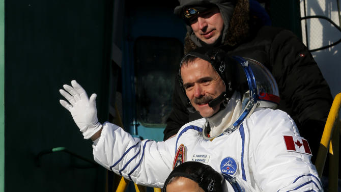 U.S. astronaut Thomas Marshburn, center, Russian cosmonaut Roman Romanenko, bottom, and Canadian astronaut Chris Hadfield, crew members of the mission to the International Space Station, gesture prior to the launch of the Soyuz-FG rocket at the Russian leased Baikonur cosmodrome, Kazakhstan, Wednesday, Dec. 19, 2012. (AP Photo/Dmitry Lovetsky, Pool)