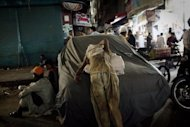 A Pakistani street child and scavenger is seen resting on a covered car in Karachi. According to charities which work to protect street children in Pakistan, up to 90 percent are sexually abused on the first night that they sleep rough and 60 percent accuse police of sexually abusing them