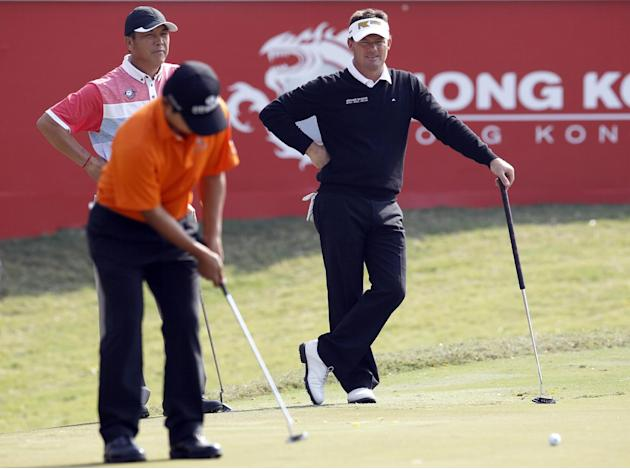 Alex Cejka of Germany, right, watches Kang Sung-hoon of South Korea, front left, hitting a putt on the 18th hole on the second round of the Hong Kong Open golf tournament in Hong Kong Friday, Dec. 6,