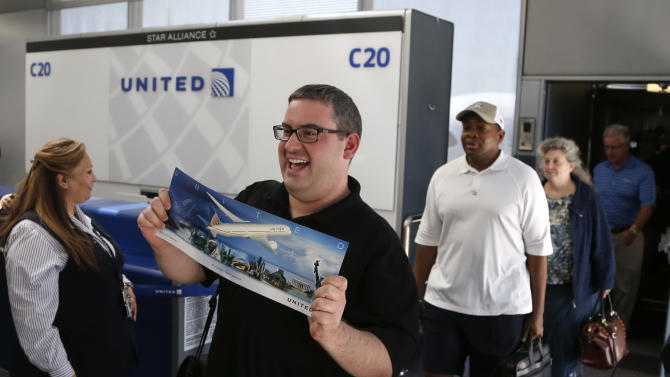 A passenger on United Airlines Flight # 1 a Boeing 787 Dreamliner aircraft arrives displaying his commemorative poster of the flight at Chicago's O'Hare International Airport Monday, May 20, 2013.  The planes are returning after being grounded for four months by the federal government because of smoldering batteries on 787s owned by other airlines. (AP Photo/Charles Rex Arbogast)