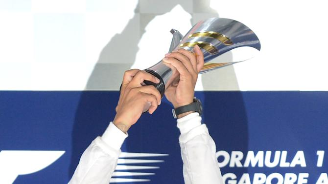 Mercedes driver Lewis Hamilton of Britain lifts up his winning trophy on the podium after the Formula One Singapore Grand Prix at the Marina Bay street circuit on September 21, 2014